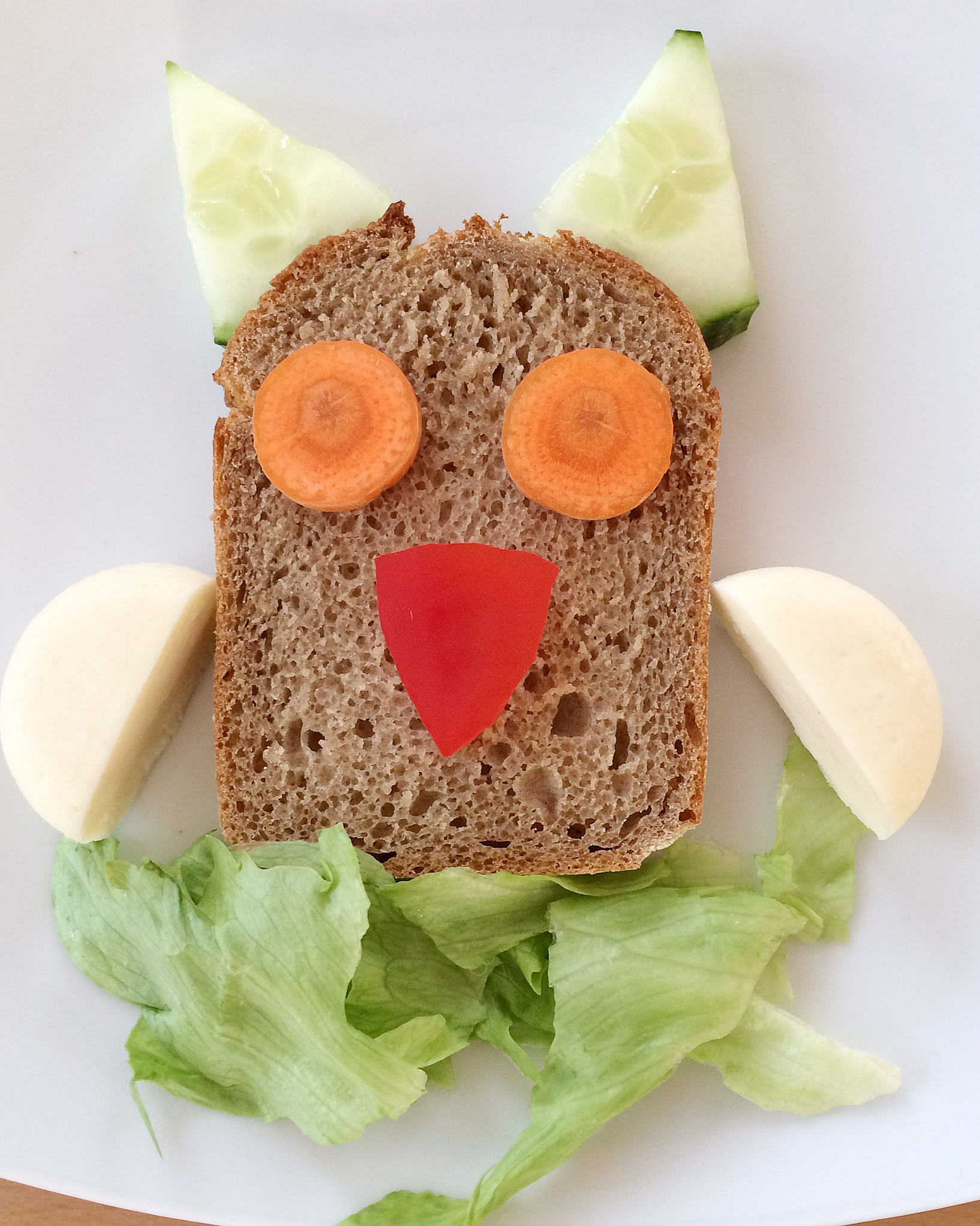 Schnell gemachte Eule. Aus Brot, Salatgurke, Karotte, Mini-Babybel, Eisbergsalat.