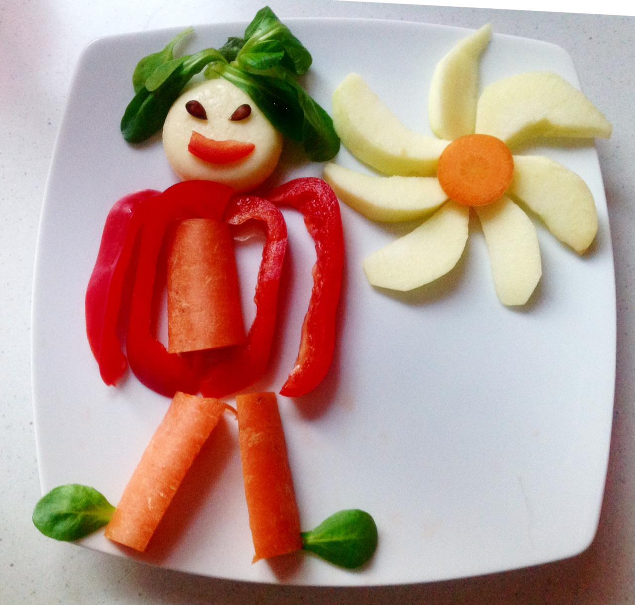 Ein schnell geschnitztes Männchen aus Paprika und Karotte, mit Feldsalat, Apfel und Mini-Babybel.