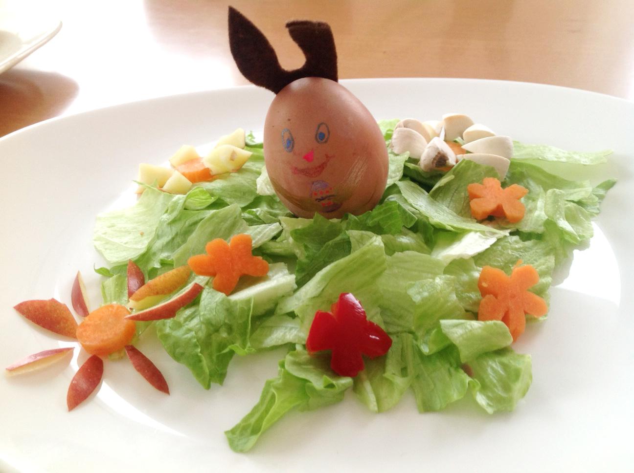 Osterabendmenübeilage made by Mama. Hase aus Ei sitzt auf Eisbergsalatwiese mit Blumen aus Karotte, Paprika, Apfel und Champignon.