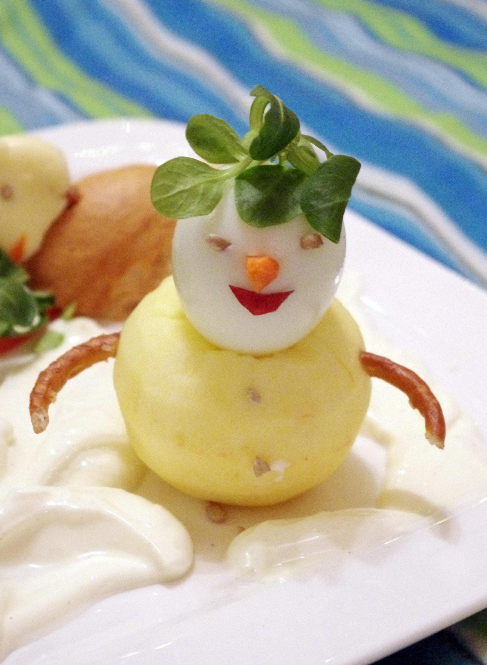 Schneemann aus Apfel, Ei, Feldsalat, Salzbrezel, Karotte und Paprika.