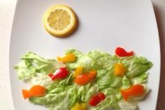 schnell geschnitzte Fische aus Paprika im Eisbergsalatmeer unter einer Zitronensonne.
