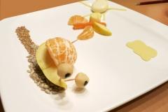 Töchterchens Création. Schnecke aus Apfel und Mandarine mit Marzipanaugen kriecht auf einem Weg aus Sonnenblumenkernen. Im Hintergrund Schmetterling und Sonne und Wolke aus Käse.