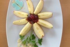 Schnell gemacht: Kleine Blume aus Apfelschnitzen mit Weintrauben, Petersilienblättern auf Mandeln.