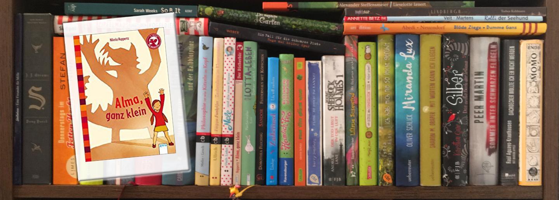 Alma ganz klein vor Bücherregal