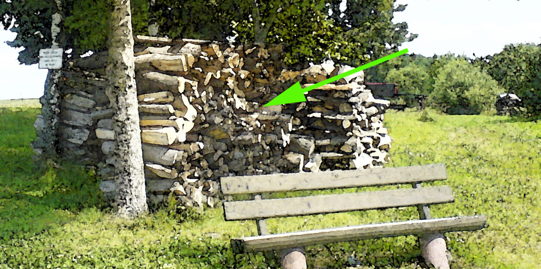 Foto Bank mit Holzstapel dahinter und Pfeil für Schatzsuche