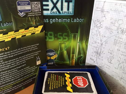 Exit- Das geheime Labor. Verpackung, Spielanleitung und Karten in der Box.