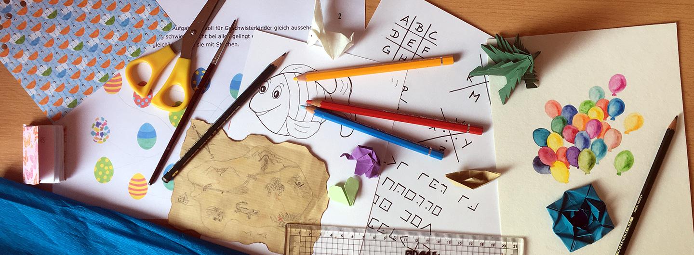 Bunstifte, Origamis, Papiere, Schere, Lineal, Ausmalbild, Schatzkarte bunt durcheinander gewürfelt.